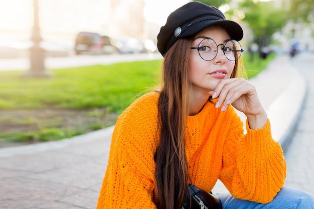 かわいい丸いメガネの物思いに沈んだブルネット白い学生女性のライフスタイルの肖像画を間近します。