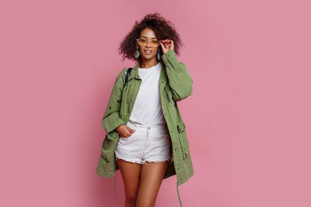 緑のジャケットがピンクの背景にポーズでかなりスタイリッシュな黒の女の子。冬や春のファッションルック。
