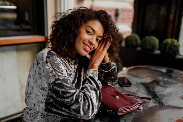 Закройте вверх по портрету образа жизни задумчивой чернокожей женщины наслаждаясь перерывом на чашку кофе в париже.
