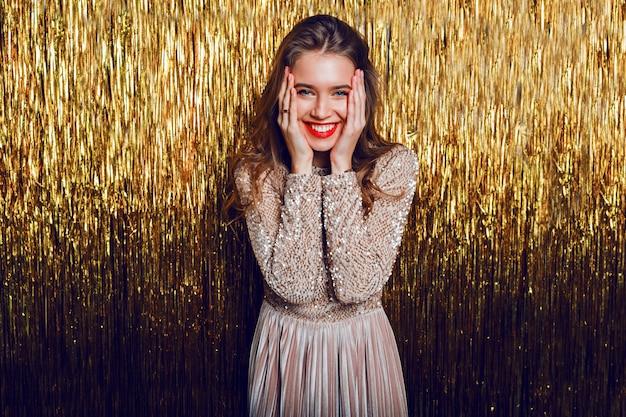 黄金の輝く上に立っている驚きの顔を持つエレガントな祝う女性