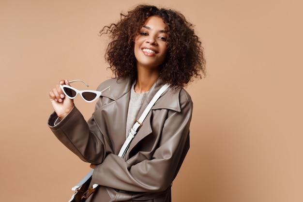 ベージュ色の背景にポーズをとって灰色の革のコートを着ている格好良い黒人女性。秋や冬のファッションのコンセプトです。