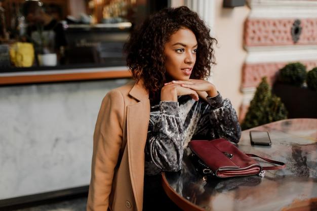 パリのカフェに座っているスタイリッシュなアフロの毛を持つ美しい笑顔の黒人女性の屋外のポートレート。