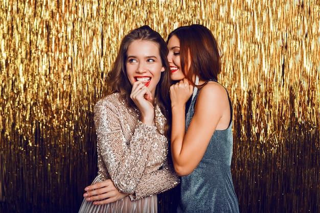 Две празднующие девушки в элегантном вечернем платье позируют на золотой череде