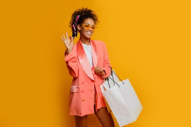 黄色の背景の上に白いショッピングバッグ立って幸せな黒人女性。トレンディな春のおしゃれな表情。
