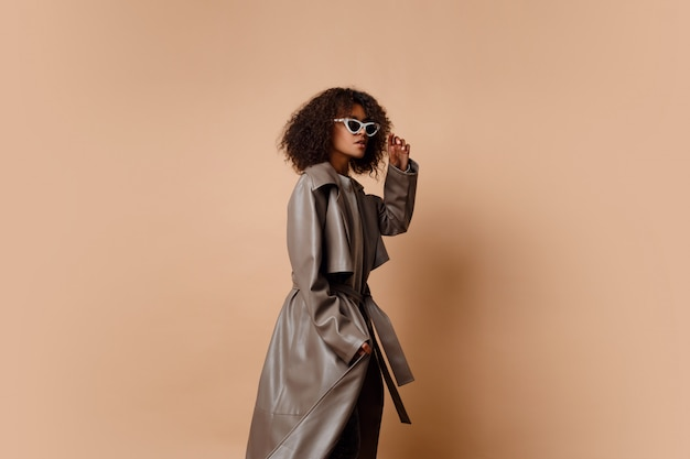 Чернокожая женщина в ультрамодной серой кожаной куртке представляя над бежевой предпосылкой в студии. зимняя и осенняя мода смотрятся.