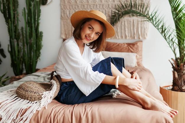 自由奔放に生きるスタイルのスタイリッシュなフラットで晴れた朝を楽しんでいるベッドに座っている率直な笑顔でロマンチックな女性