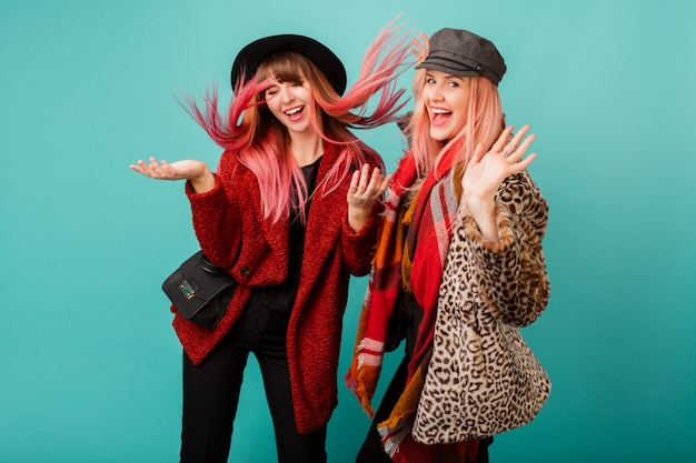 Две красивые женщины в стильных шубах из искусственного меха и шерстяном шарфе позируют на бирюзовой стене