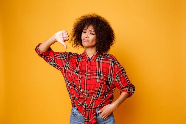 オレンジ色の背景の上に立っている若い黒人女性を動揺して親指を下げます。赤いシャツとジーンズを着ています。