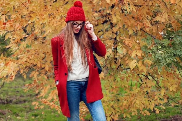 トレンディなカジュアルな服装で日当たりの良い秋の公園を歩いて長い髪のブロンドの女性。