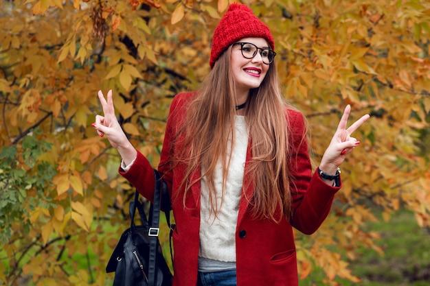 Улыбающаяся белокурая женщина с длинными волосами, идущими в солнечном осеннем парке в модном случайном оборудовании.