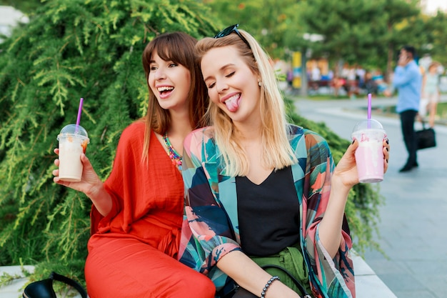 一緒に楽しんで、日当たりの良い近代的な都市での休日を楽しんでいる親友
