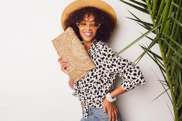 トレンディなブラウスと麦わら帽子立っている白い壁の上でファッショナブルなミックスレースの女の子。完璧な白い笑顔。ショッピング気分。