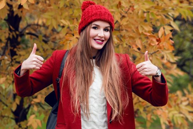 Счастливая успешная белокурая женщина в красной шляпе и куртке представляя в парке осени.