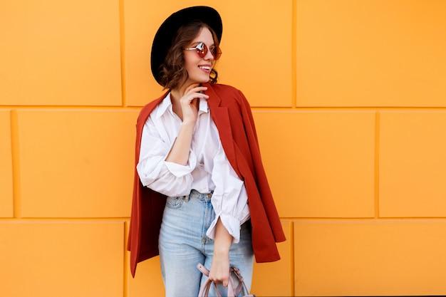 黄色の壁を越えてポーズスタイリッシュな帽子でかなりブルネットの少女。