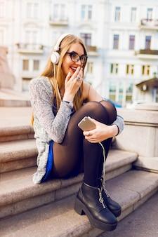 イヤホンで音楽を聴く、携帯電話を保持している、通りに座っている、夢を見てかなり若いブロンドの女性の夏のライフスタイルの日当たりの良いイメージ。スタイリッシュな春服を着ています。