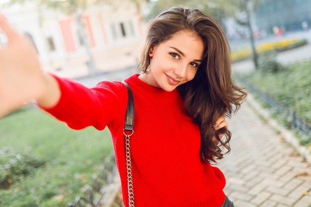 魅力的な若いブルネットの女性が携帯電話でセルフポートレートを作って、公園を歩いて、楽しんでいます。赤いカジュアルプルオーバー。ライフスタイル。フレッシュメイク。ウェーブのかかった髪型。