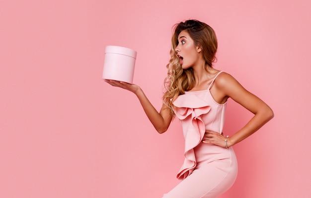 驚きの顔のギフトボックスを押しながらエレガントなピンクのドレスでバラの壁に立っているグラマーブロンドの女の子。恍惚とした感情。