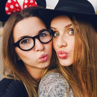 Крупным планом образ жизни милый портрет двух лучших друзей, делая автопортрет, весело, улыбаясь. наслаждаясь временем вместе, настроением весеннего сезона. естественный макияж. блондинки и брюнетки. стильная шапка.