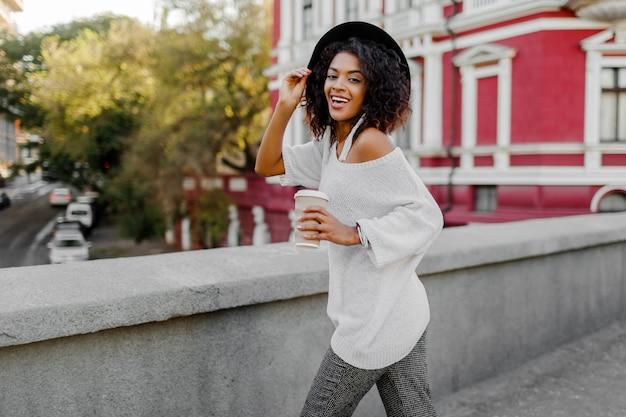 スタイリッシュなアフロの毛と街を歩いて、飲み物のカップを保持している黒い帽子の屈託のない黒人女性。カジュアルな服装。完璧な率直な笑顔。楽しんでください。