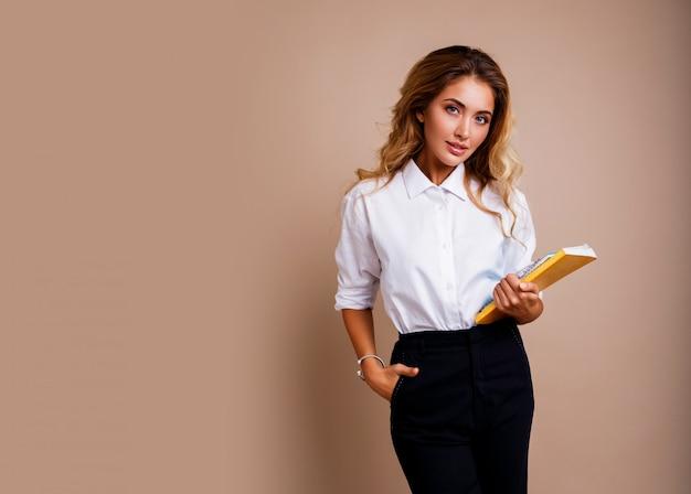 Деловая женщина в стильных очках, держащих книги и стоящих по бежевой стене. светлые волнистые волосы. белая блузка и черные брюки.