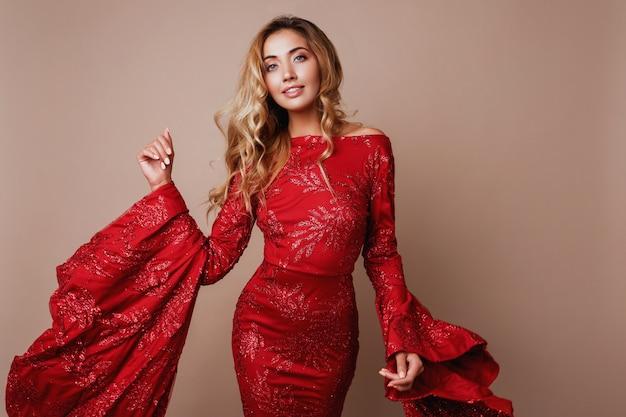 ワイドスリーブの豪華な赤いドレスでポーズをとって魅惑的なブロンドの女性。おしゃれな表情。ブロンドのウェーブのかかった髪。