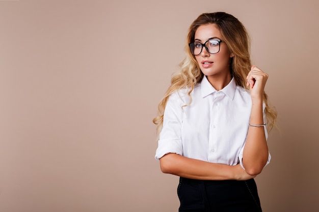 思いやりのある金髪女性がポーズベージュの壁に分離します。スタイリッシュなカジュアルワークウェア。