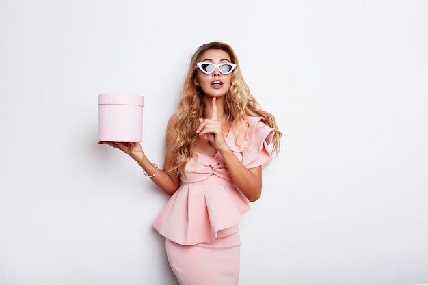 魅惑的なブロンドの女性がギフトボックスを押し、白い壁にピンクのドレスでポーズします。ショッピングと祝うコンセプト。おしゃれなサングラス。