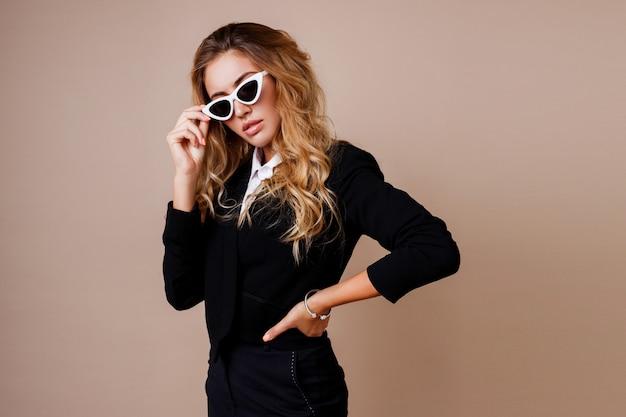 Фасонируйте портрет шикарной белокурой женщины в стильной вскользь черной куртке представляя на бежевой стене. белые ретро очки. высокий модный вид.