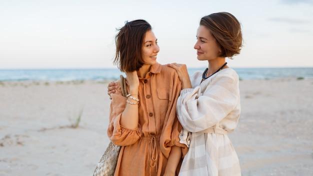 ビーチでポーズリネンの夏服で短い髪型とカップルします。