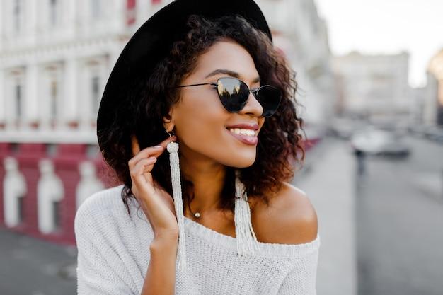 良い一日を楽しんでいるトレンディな服装の官能的なアフリカの女性