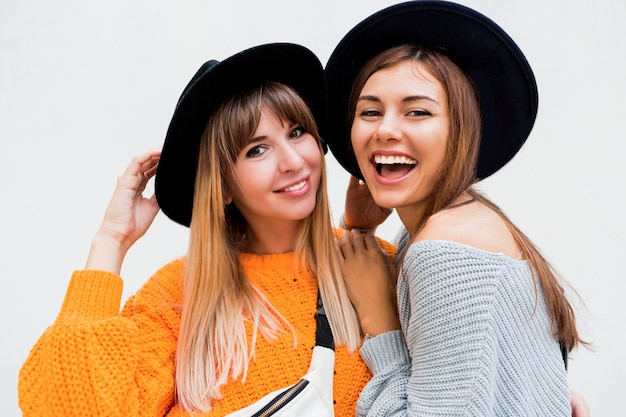 Две беззаботные девушки посылают воздушный поцелуй в камеру, стоя на белом