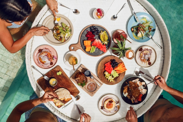 スイミングプールのフローティングトレイでトロピカルな朝食を持っている友人のグループ。新鮮なエキゾチックなフルーツとドリンク。パーティー気分。