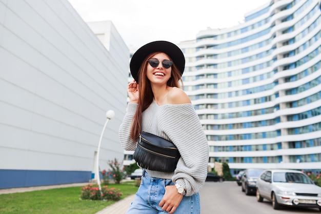 黒いウールの帽子と灰色の秋のセータージャンプと近代的な都市で散歩を楽しんでいるうれしそうな女の子の屋外イメージ。