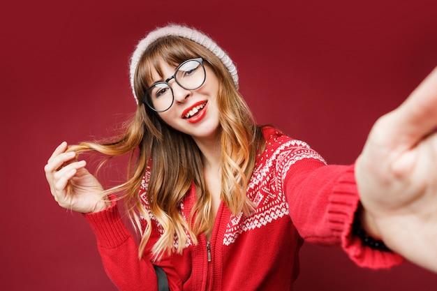 冬の服で幸せな長い髪の女のセルフポートレート