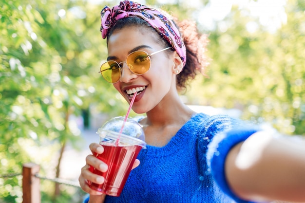 セルフポートレートを作るかわいい笑顔の流行に敏感な黒人女性のセルフポートレートを閉じます