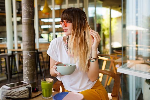 Счастливая стильная женщина ест здоровую пищу, сидя в красивом интерьере с зелеными цветами