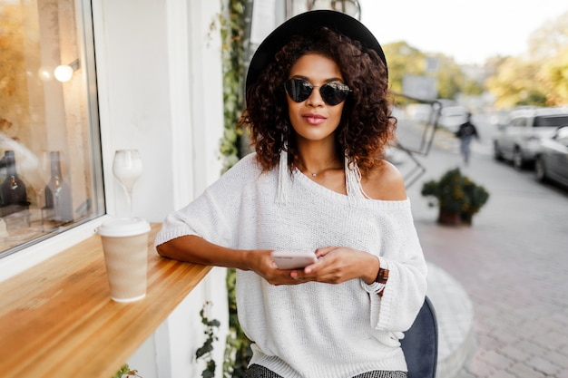 Путешествие смешанной расы женщина в стильный случайный наряд расслабляющий открытый в городском кафе, пить кофе и общаться в чате по мобильному телефону.