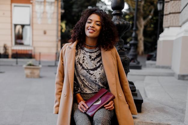 Модная черная девушка в изумительном сером бархатном свитере, бежевом шерстяном пальто, роскошных ювелирных аксессуарах гуляет по парижу возле театра.