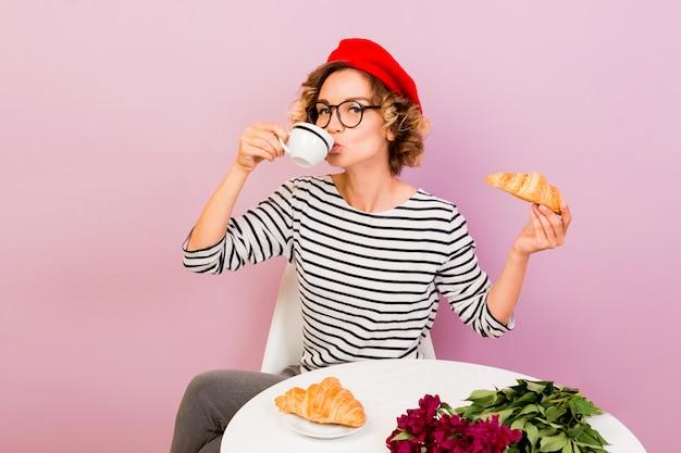 Счастливая путешествующая женщина во франции ест круассаны с кофе, сидит за столом на розовом.