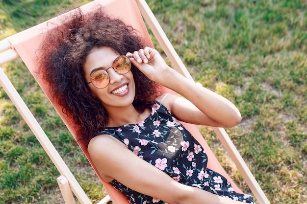 素晴らしい緑の芝生の長椅子に座っているスタイリッシュな巻き毛のヘアスタイルと幸せなファッショナブルな黒人女性