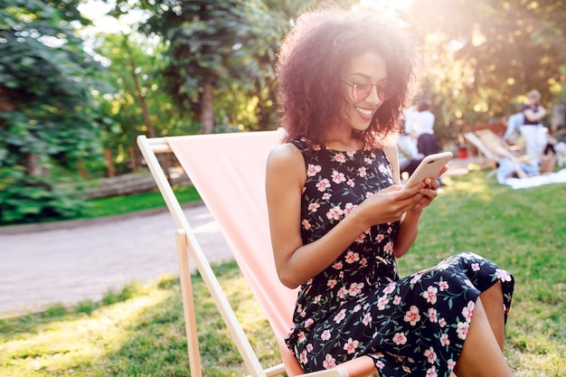 芝生の寝椅子と携帯電話のテキストメッセージに座っている混血の少女。
