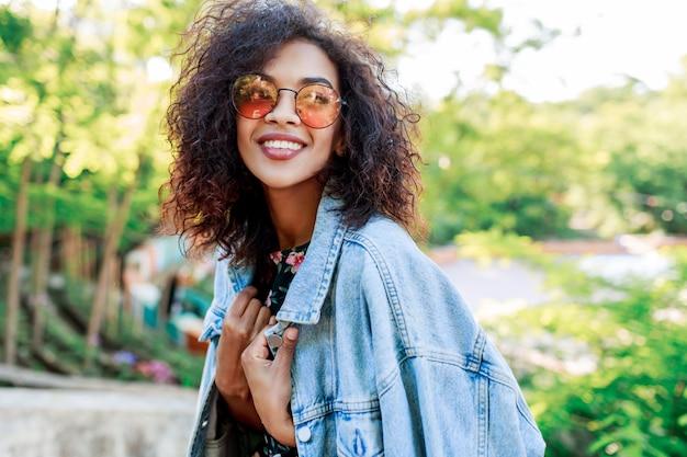 Смешанная раса красивая женщина с идеальными зубами и волосами проводит свой досуг в парке