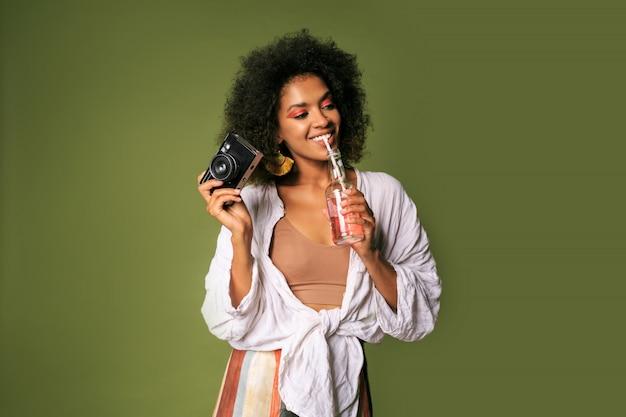 Довольно африканская женщина с афро прической, пить лимонад из соломы. летний стиль. яркий макияж.