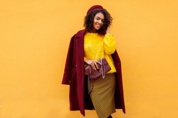 Модная девушка в удивительном зимнем наряде и аксессуарах позирует на желтом