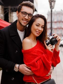 幸せな美しいカップル恥ずかしいと休日に路上でポーズします。ロマンチックな気分。フィルムカメラを保持しているブルネットの女性。