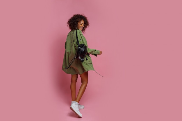 ピンクの背景のスタイリッシュな緑のジャケットに褐色肌の格好の良い女性の完全な長さの画像。ショッピングとファッションのコンセプトです。