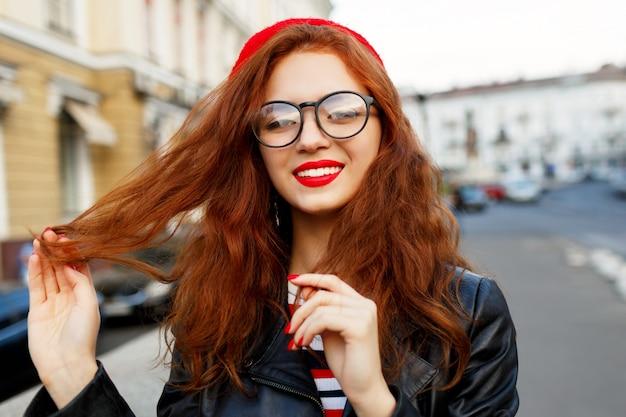 Счастливая сказочная рыжая женщина в стильном красном берете на улице