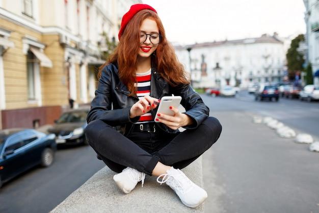 Счастливая сказочная рыжая женщина в стильном красном берете на улице с помощью смартфона