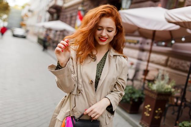 赤い髪と明るい美しい女性が通りを歩いて占めています。ベージュのコートとグリーンのドレスを着ています。