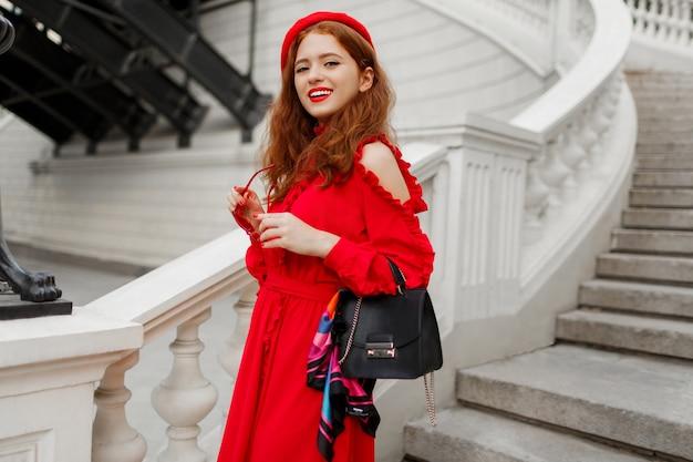 Портрет модная рыжая женщина в красном берете и элегантное платье позирует на улице.